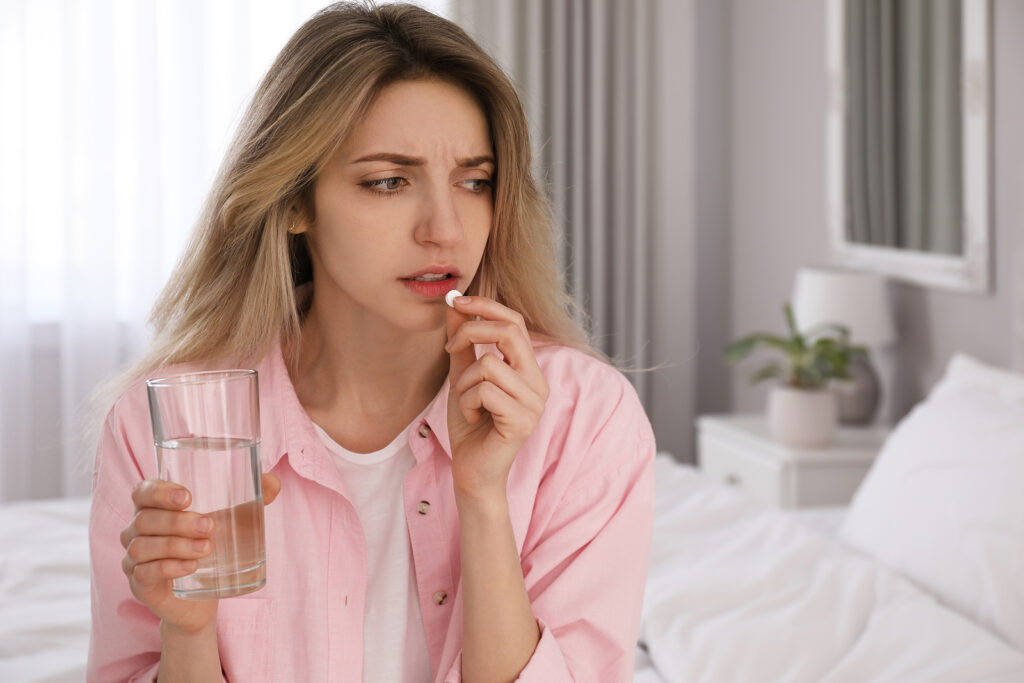 Upset young woman taking abortion pill at home